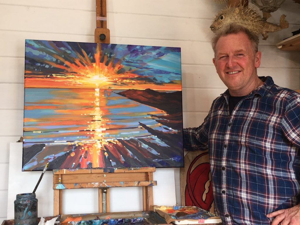 Woolacombe artist Steve PP standing at his easel in front a beautiful uplifting sunset painting.